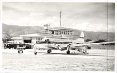 """(Ephemera) New Zealand National Airways Corporation's DH 114 Heron, ZK-ABO """"Mako"""" on tarmac, beside control tower at Nelson airport, March 27th, 1953. B&W photo with technical details verso. 9x14 cm."""