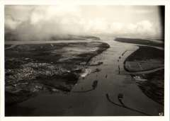 """(Ephemera) Graf Zeppelin, original B&W photograph 16x12cm, issued by the Zeppelin Company, from a series taken during the maiden flight of the Graf Zeppelin to South America. Number 12, """"Flying over Huelva, a coastal town 80 miles SW of Seville"""". A list of the Photograph in this series, which confirms the location of this particular picture, accompanies this item."""