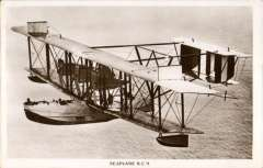 """(Ephemera) The NC 9 seaplane in flight, an original unused sepia photocard in fine condition. Manufacture of the """"NCs"""" began in 1918 during WW. The U.S. Navy wanted an aircraft capable of long ocean flights for anti-submarine warfare patrol and, if possible, with the capability to fly across the Atlantic Ocean under their own power to avoid having to be shipped through ocean waters menaced by German submarines. The Navy and Curtiss designed one of the largest biplanes yet produced, and powered by threeengines. Maximum speed was 90 mph with a maximum range of 1,500 miles."""