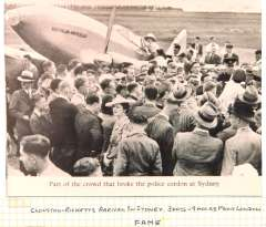 """(Ephemera) Clouston and Ricketts arriving in Sydney three days and nine hours after their second, and this time successful  attempt on the England-Australia record which began on March 15. The plane, a DH Comet, which had been renamed  """"Australian Anniversary"""" for the Australian sesquicentenial, is shown surrounded by a crowd of well wishers who had broken through the police cordon.. B&W photo, 12x9cm."""