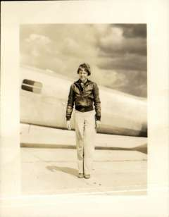 (Ephemera) Amelia Erhart wearing flying jacket and standing alongside fuselage of unknown plane, full length photograph made from the original negative,10x13cm.