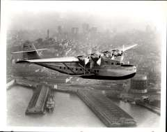(Ephemera) China Clipper flying gracefully over docks with city buildings in background, B&W photograph of the period, 23x19cm. A beautiful and evocative photo.
