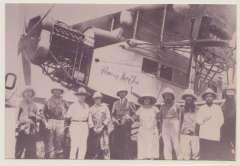 """(Ephemera) The Handley Page """"Princesse Marie Jose"""" arriving in Leopoldville on April 3, 1925, sepia photograph ,15x10cm, showing plane and group of nine local dignitaries, among whom is like to be the pilot Lt. Thieffry."""