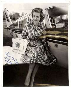 """(Ephemera) Sheila Scott, superb original B&W publicity photograph standing alongside her famous Piper Comanche G-ATOY Sheila Scott and Myth Too""""  record breaking plane, and signed 'Good Wishes, Sheila Scott'."""