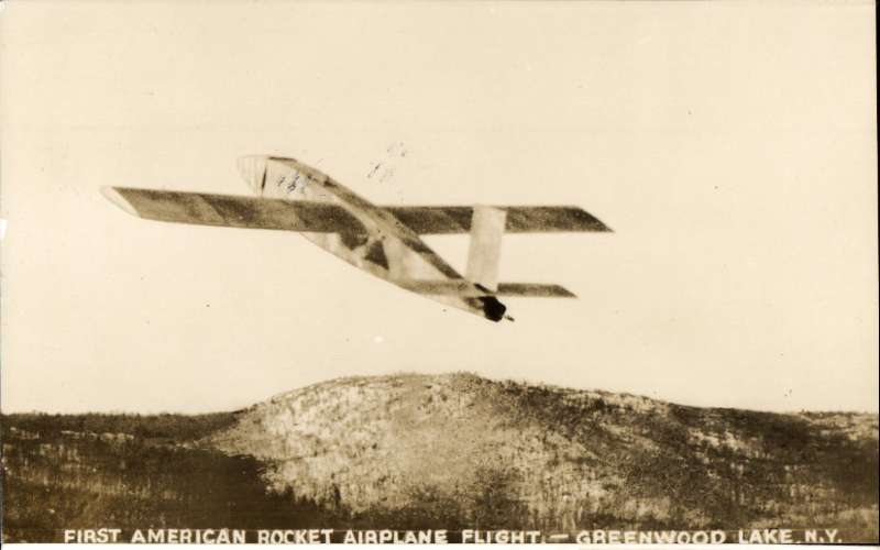 (United States Internal) First US Airplane Rocket Flight, Greenwood Lake, souvenir sepia  photocard, Green cachet tying red vignette, verso photo of rocket plane in flight. Image.